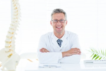 Doctor sitting at his desk smiling at camera