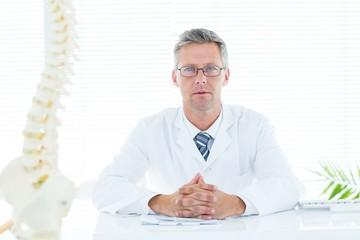 Doctor sitting at his desk looking at camera