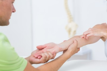 Doctor examining his patients arm
