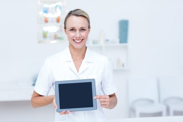 Smiling doctor looking at camera and showing tablet