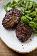 Beef cutlets with beans, close-up, above view