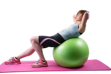 Pretty brunette exercising on fitness ball
