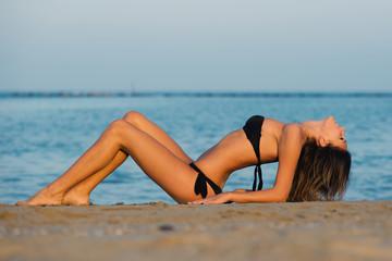 Sensual woman wearing black bikini laying on the beach at sunset