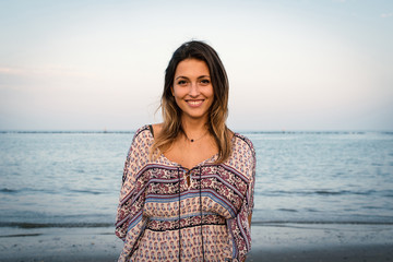 Beautiful young woman smiling portrait at the beach with sea in