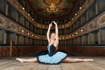 Young classical ballerina dancing inside old theater of Ripatran