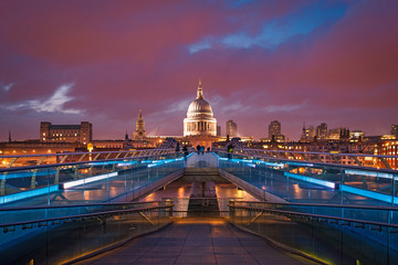 People walking over Millennium bridge at dusk. St Pauls cathedra