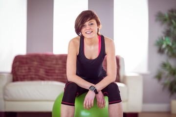 Fit woman sitting on exercise ball