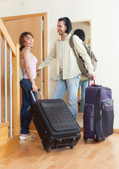 positive couple with luggage in home going