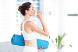 Brunette drinking water while holding exercise mat