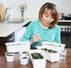 woman in green working with  seedlings