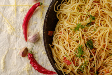 Spaghetti Pasta in airon frying pan with garlic, tomatoes and sp