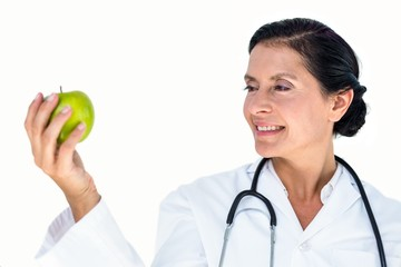 Confident female doctor holding green apple