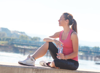 Young woman sitting on the riverbank and resting after jogging.