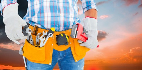 Composite image of midsection of handyman holding hand tools