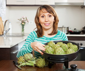 Woman cooking artichoke in kitchen