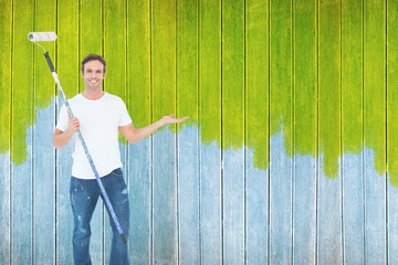 Composite image of man gesturing while holding paint roller