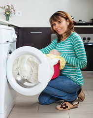 Happy housewife using washing machine