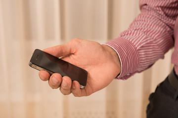 Working in digital age. Close-up of man holding a smartphone