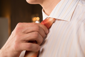 man in formalwear adjusting his necktie