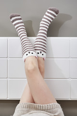 Woman legs raised up on bed wearing bear lined socks.