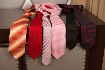 neckties in different colors lying on the dresser