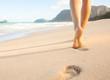 Leinwanddruck Bild - Woman walking on sandy beach leaving footprints in the sand.
