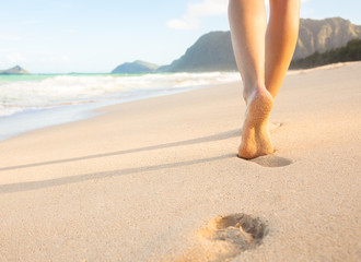 Woman walking on sandy beach leaving footprints in the sand.