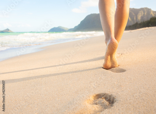 Woman walking on sandy beach leaving footprints in the sand. - 82100657