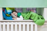 Young child sleeping on the windowsill over heating radiator