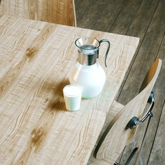Vintage jug and glass full of milk on wooden table