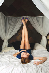 Young woman lying and holding her legs up