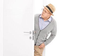 Curious senior looking at something behind a door