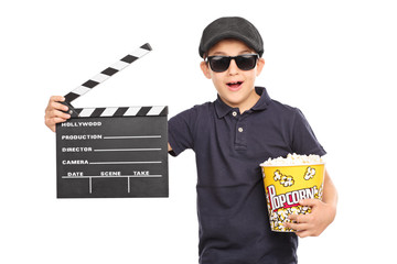 Little kid holding popcorn and a clapperboard