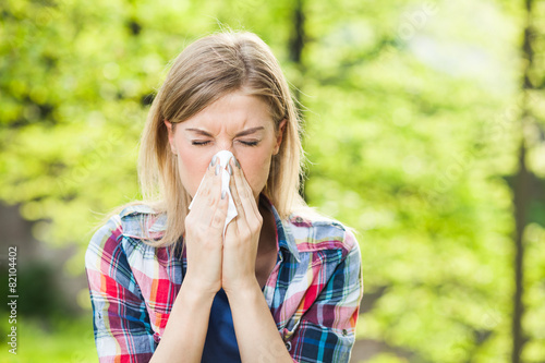 Woman with allergy symptom blowing nose - 82104402