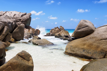 Tropical beach with spraying wave and rocks