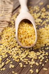 Natural healthy bulgur asian wheat grain in spoon on vintage bac