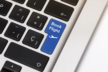 """Laptop key showing the words """"book flight"""", in blue color."""