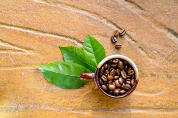 Coffee beans in a mug with leaves top view