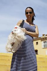 Mujer morena con su perrito colgando del hombro