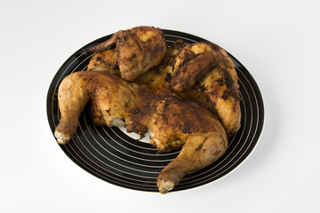 Roasted chicken on a striped black dish