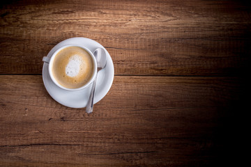 Cup of freshly brewed aromatic cappuccino standing on a wooden t