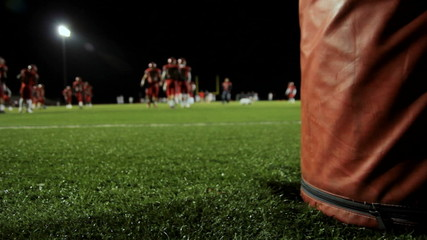 Behind a goalpost as football players warm up before a game.