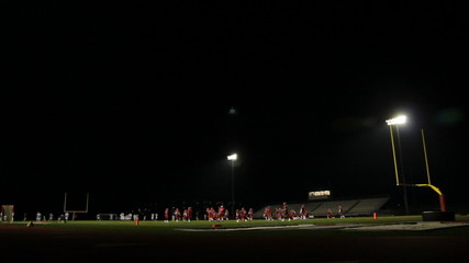 Wide shot of high school football players warming up at night.