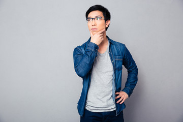 Pensive asian man standing over gray background