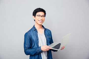 Smiling asian man standing with laptop