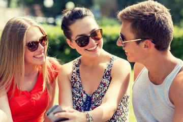 smiling friends with smartphone sitting in park