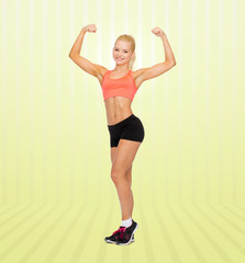 smiling sporty woman showing her biceps