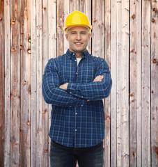 smiling male builder or manual worker in helmet