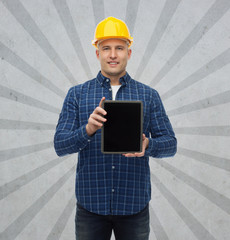smiling male builder in helmet with tablet pc