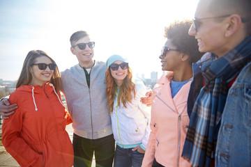 happy teenage friends in shades talking on street